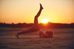 Young woman is doing yoga asana Eka Pada Ashtanga Namaskarasana - eight limbed salutation pose in the desert at sunset.  royalty free stock images