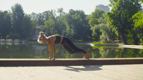 Young woman doing yoga asana - virasana. In the park against lake at summer day stock video footage