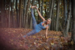 Young woman doing yoga asanas in autumn forest. Young blond woman with braid doing yoga asanas in autumn forest Royalty Free Stock Images