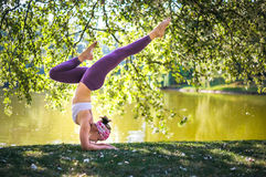 Young woman doing yoga balance in Park near lake Stock Photo