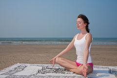 Young woman doing yoga on the beach Stock Image
