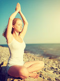 Young woman doing yoga on  beach Stock Photos