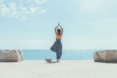 Young woman doing yoga in the beach. Royalty Free Stock Image