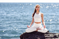 Young woman doing yoga in the beach wearing white clothes Stock Image