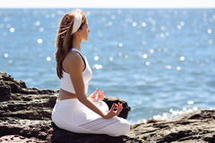 Young woman doing yoga in the beach wearing white clothes Stock Images