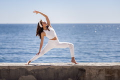 Young woman doing yoga in the beach wearing white clothes Stock Photos