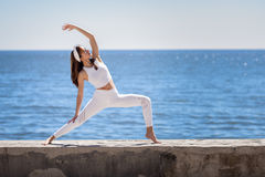 Young woman doing yoga in the beach wearing white clothes Royalty Free Stock Image