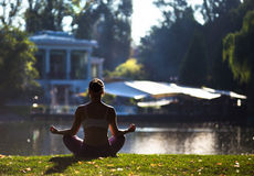 Young woman doing yoga in beautiful morning near lake Royalty Free Stock Photography