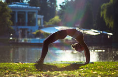 Young woman doing yoga in beautiful morning near lake Stock Images