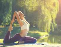 Young woman doing yoga in beautiful morning near lake Royalty Free Stock Image