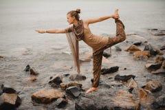 Young woman doing yoga on coast of sea Stock Photo