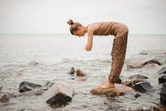 Young woman doing yoga on coast of sea Stock Photography