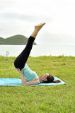 Young woman doing yoga on coast of sea. On beach Stock Photos