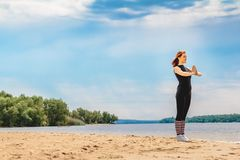 Young woman doing yoga on coast of sea on beach stock photo