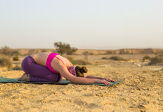 Young woman doing yoga in desert at sunrise time Stock Images