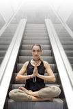 Young Woman Doing Yoga on the Escalator, Sitting in Lotus Posture. Stress Free Concept. Young Woman Doing Yoga on the Escalator, Sitting in Nice Lotus Posture Stock Images