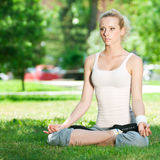 Young woman doing yoga exercise. Beautiful young woman doing stretching exercise on green grass at park. Yoga Stock Images
