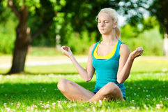 Young woman doing yoga exercise. Beautiful young woman doing stretching exercise on green grass at park. Yoga Royalty Free Stock Photography