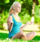 Young woman doing yoga exercise. Beautiful young woman doing stretching exercise on green grass at park. Yoga Stock Photos