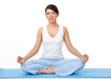 Young woman doing yoga exercise on blue mat Stock Images