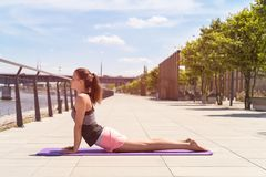Young woman doing yoga exercise on mat. Young woman doing yoga exercise on mat in the city Stock Image