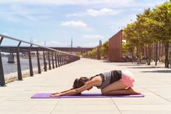 Young woman doing yoga exercise on mat. Young woman doing yoga exercise on mat in the city Royalty Free Stock Photos