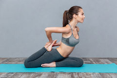 Young woman doing yoga exercise one legged king pigeon Stock Photos