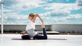 Young woman doing yoga exercise one legged king pigeon pose in slow motion. Flexible girl is doing stretching in background of white clouds and bright blue sky stock footage