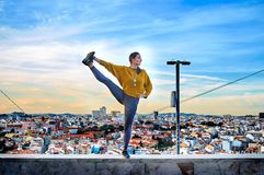 Young woman doing yoga exercise outdoors on the Lisbon city view background. Urban yoga royalty free stock images