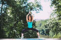 Young woman doing yoga exercise in park. Stock Photos