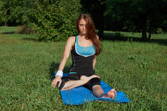 Young woman doing yoga exercise on park Stock Images