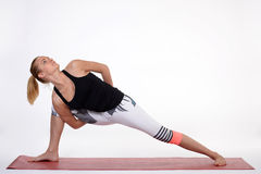 Young woman doing yoga exercise on red mat. Royalty Free Stock Photos