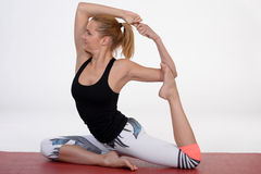 Young woman doing yoga exercise on red mat. Stock Photography