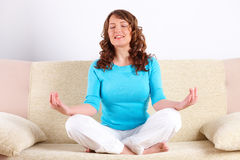 Young woman doing yoga exercise on sofa Stock Photo