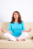 Young woman doing yoga exercise on sofa Stock Image