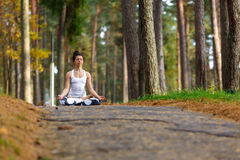 Young woman doing yoga exercises in the autumn city park. Health lifestyle concept. stock photo