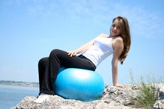 Young woman doing yoga exercises with the ball Stock Photo