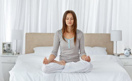 Young woman doing yoga exercises on the bed Royalty Free Stock Image
