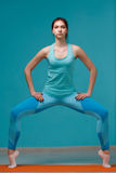 Young woman doing yoga exercises. On blue background Stock Photography