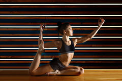 Young woman doing yoga exercises in dark studio. Health lifestyle concept. Royalty Free Stock Images