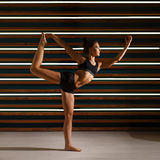 Young woman doing yoga exercises in dark studio. Health lifestyle concept. Royalty Free Stock Photo