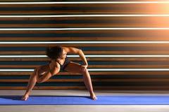 Young woman doing yoga exercises in dark studio. Health lifestyle concept. Stock Photo