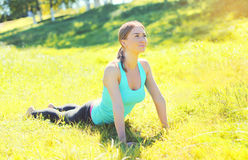 Young woman doing yoga exercises on grass in summer Stock Photos