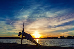 Young woman doing yoga exercises on the lake beach at sunset royalty free stock photo