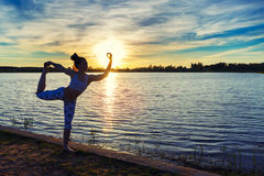 Young woman doing yoga exercises on the lake beach at sunset royalty free stock photography