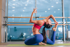 Young woman doing yoga exercises on mat at gym royalty free stock image