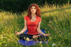 Young woman doing yoga exercises in the nature Royalty Free Stock Photos