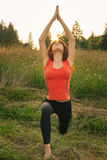 Young woman doing yoga exercises in the nature Stock Photo