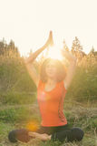 Young woman doing yoga exercises in the nature Stock Images
