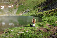 Young woman doing yoga exercises near lake Stock Photos